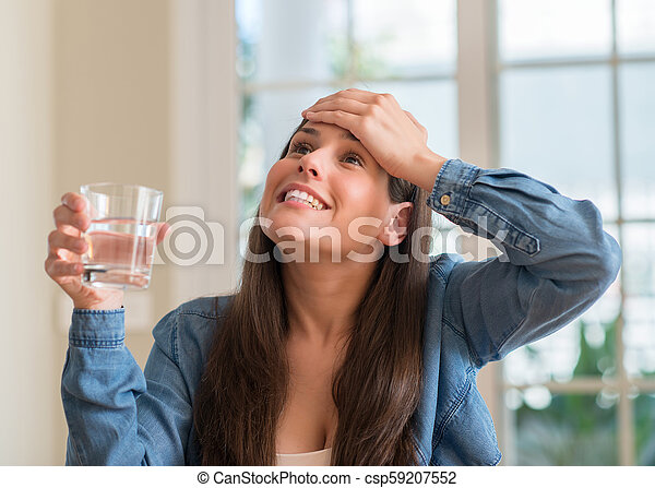 Young woman drinking glass of water at home stressed with hand on head,  shocked with shame and surprise face, angry and frustrated  Fear and upset  for