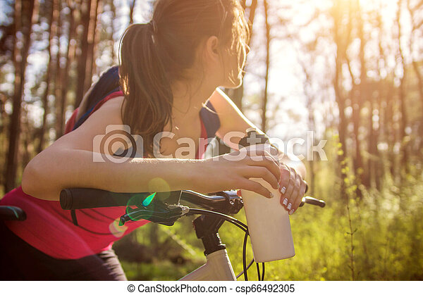 Young woman drinking water after riding a bicycle - csp66492305