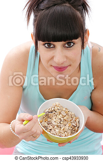 Young woman eating bowl of healthy breakfast cereal - csp43933930