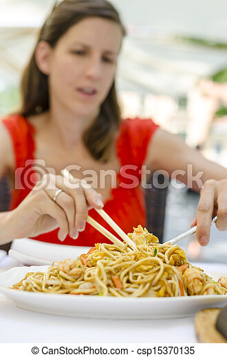 Young woman eating chinese noodles - csp15370135