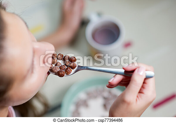 Young woman eating chocolate cereal. close-up of a spoon - csp77394486