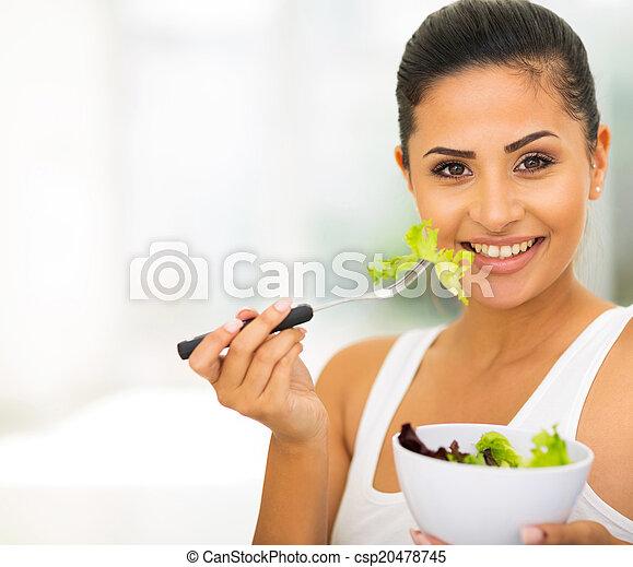 young woman eating green salad - csp20478745