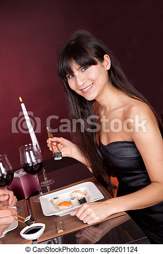 Young woman eating sushi in restaurant - csp9201124