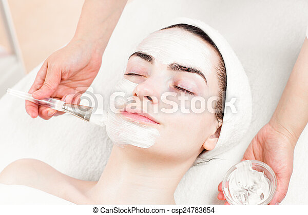 Young woman facial mask applying in beauty parlour - csp24783654