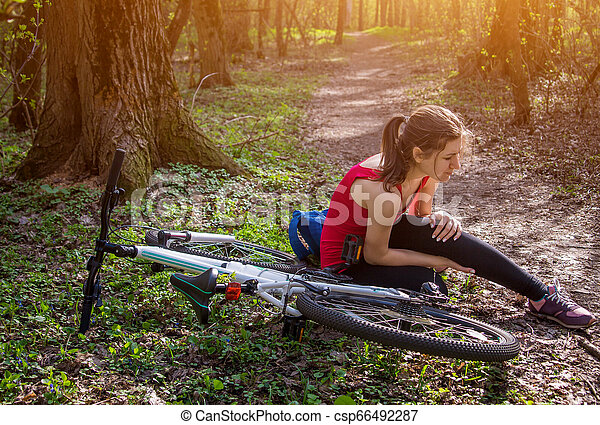 Young woman fell off the bicycle and hurt knee. Injuries and traumas during sport - csp66492287