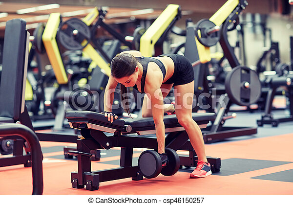 young woman flexing muscles with dumbbell in gym - csp46150257