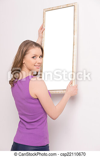 Young woman hanging mirror on wall. beautiful brunette standing near wall and looking over shoulder - csp22110670
