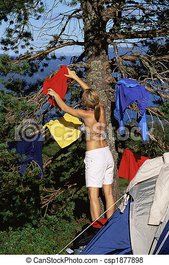 Young woman hanging out washing on a tree next to campsite - csp1877898