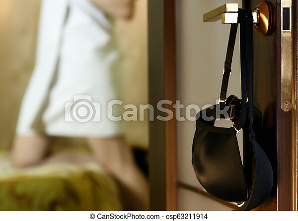 young woman hangs a bra on the door handle. sexy girl in stockings and towel in hotel room - csp63211914