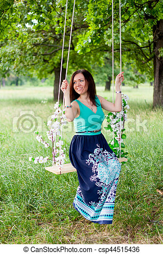 Young woman having fun swinging on a swing - csp44515436