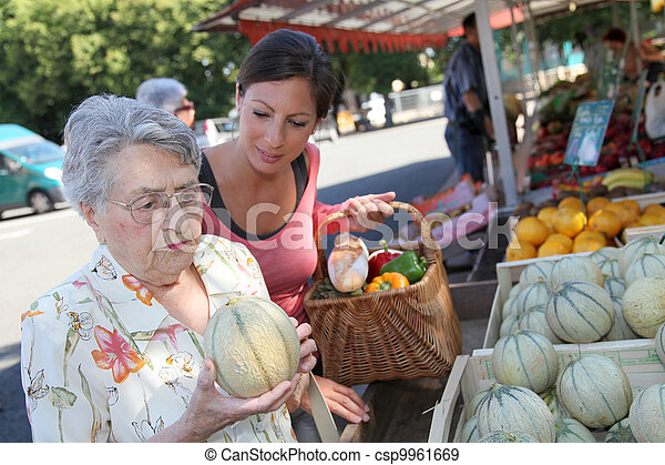 Young woman helping elderly woman with grocery shopping - csp9961669