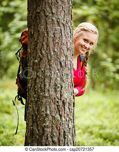 Young woman hiker behind a tree - csp20721357