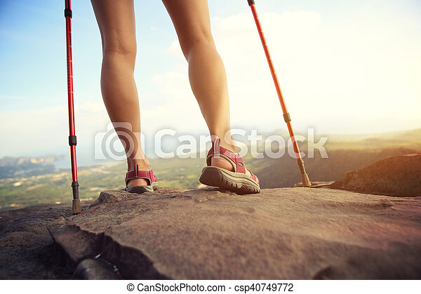 young woman hiker legs on mountain peak rock - csp40749772