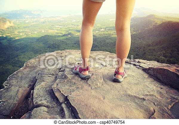 young woman hiker legs on mountain peak rock - csp40749754