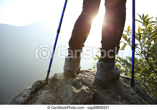young woman hiker legs on mountain peak rock - csp28809331