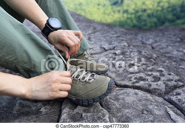 Young woman hiker tying shoelace on mountain peak - csp47773360