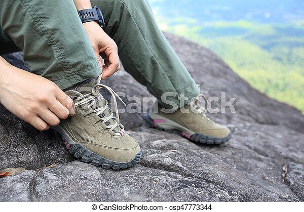 Young woman hiker tying shoelace on mountain peak - csp47773344