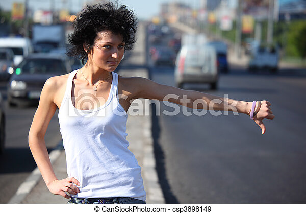 young woman hitchhiking on highway - csp3898149