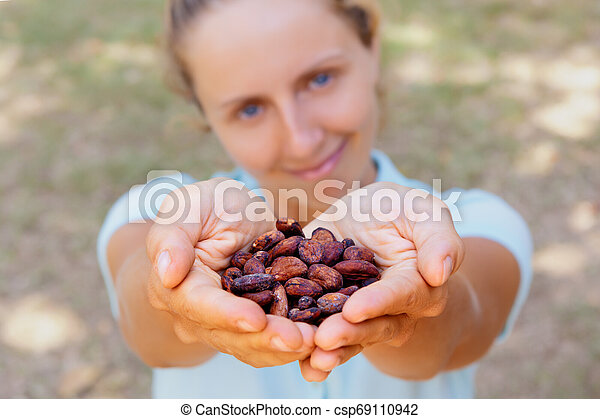 Young woman hold in hands brown dried fermented cocoa beans - csp69110942