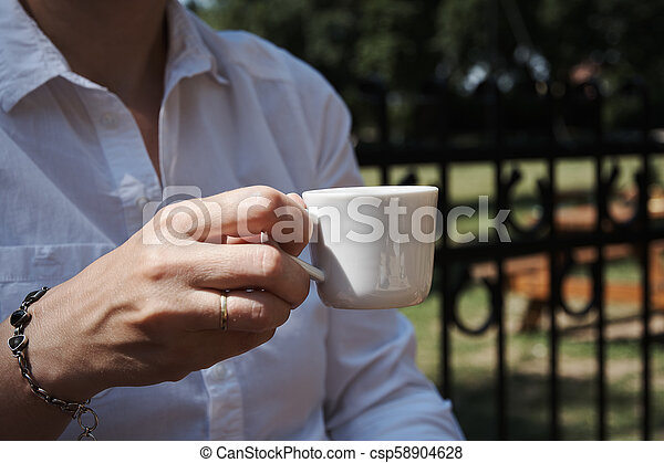 Young woman holding a cup of coffee in the garden on a sunny day - csp58904628