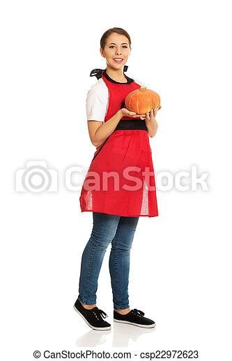 Young woman holding a pumpkin - csp22972623
