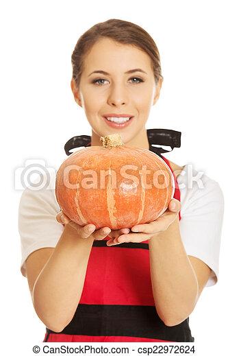 Young woman holding a pumpkin - csp22972624