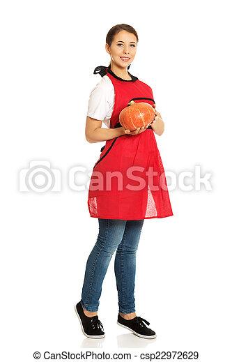 Young woman holding a pumpkin - csp22972629