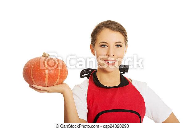 Young woman holding a pumpkin - csp24020290