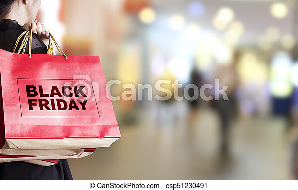 Young woman holding black friday shopping bag at department store - csp51230491