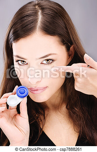 Young woman holding contact lenses cases and lens in front of her face - csp7888261
