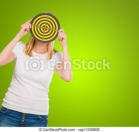Young Woman Holding Dartboard In Front Of Face - csp11036805