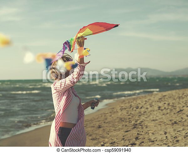Young Woman holding kite at beach on autumn day - csp59091940