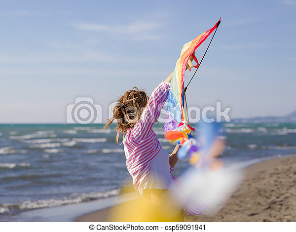 Young Woman holding kite at beach on autumn day - csp59091941