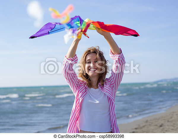 Young Woman holding kite at beach on autumn day - csp58993398