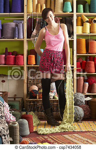 Young Woman Holding Knitted Scarf Standing In Front Of Yarn Display - csp7434058