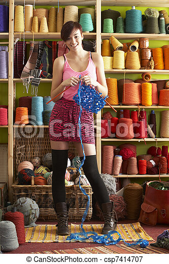 Young Woman Holding Knitting Standing In Front Of Yarn Display - csp7414707