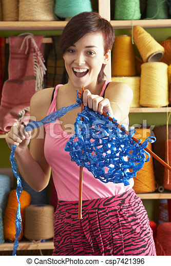 Young Woman Holding Knitting Standing In Front Of Yarn Display - csp7421396