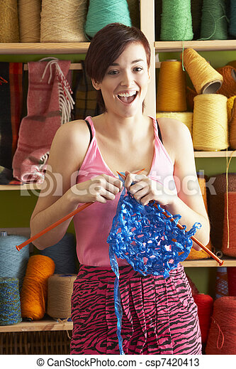 Young Woman Holding Knitting Standing In Front Of Yarn Display - csp7420413
