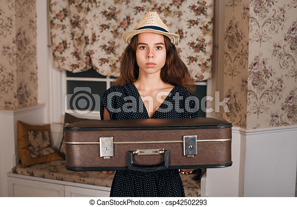 Young woman holding suitcase in her hands. - csp42502293
