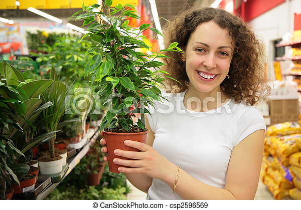 young woman holds pot with plant in shop - csp2596569
