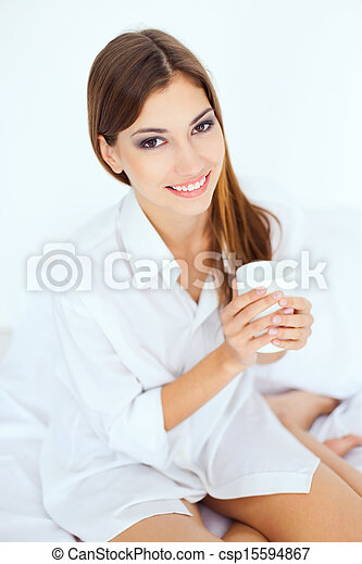 young woman in bed with a cup of coffee - csp15594867