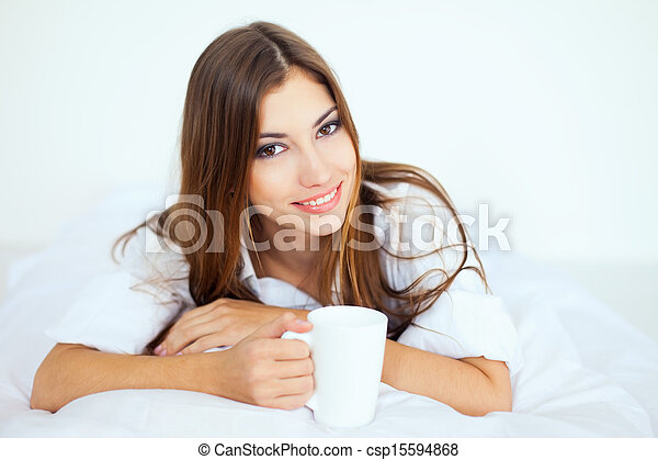 young woman in bed with a cup of coffee - csp15594868
