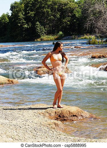 Young woman in bikini outdoors at river - csp5888995