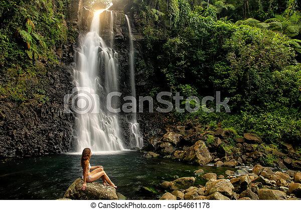 Young Woman In Bikini Sitting By Middle Tavoro Waterfalls In Bouma National Heritage Park Taveuni Island Fiji