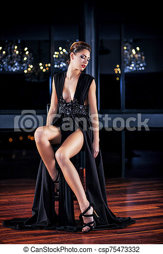 Young woman in black dress sitting on a stool - csp75473332