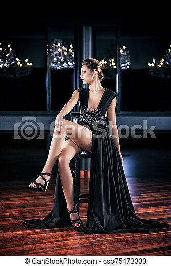 Young woman in black dress sitting on a stool - csp75473333