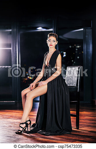 Young woman in black dress sitting on a stool - csp75473335
