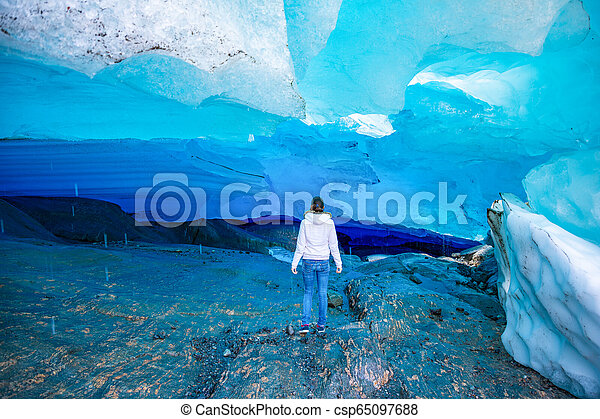 Young woman in Blue ice cave of Svartisen Glacier, Norway - csp65097688