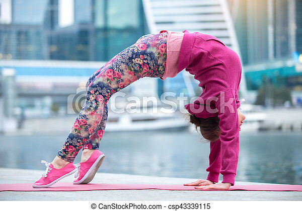 young woman in bridge pose against the city and river