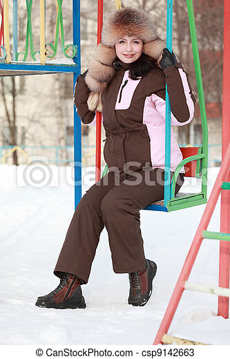 young woman in fur hat sits on swing in winter, children's playground - csp9142663